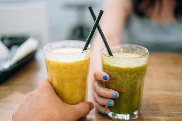 Bicchieri con frullato di frutta e verdura. uomo e donna che tengono i vetri con spinaci e frullato