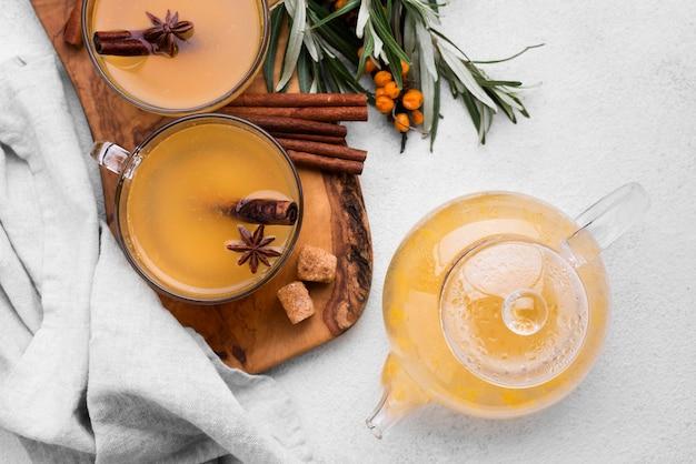 Bicchieri con succo di frutta aromatizzato e cannella sul tavolo