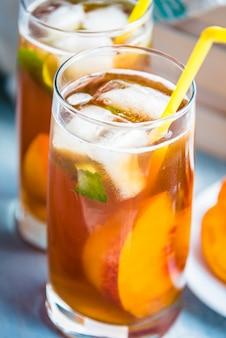 Bicchieri con tè freddo fatto in casa, aroma di pesca e fette di pesca appena tagliate per la disposizione.