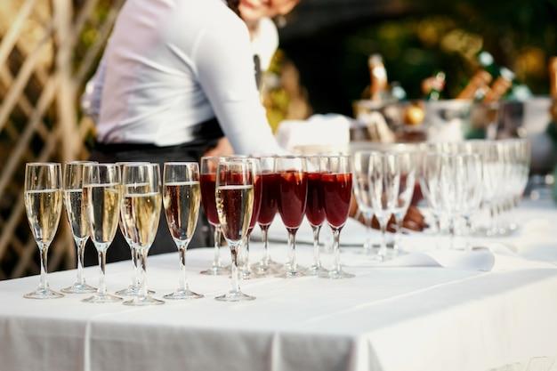 Bicchieri con vino rosso e bianco stanno sul tavolo da pranzo bianco