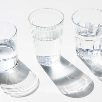 Bicchieri d'acqua con ombra scura su sfondo bianco