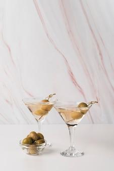 Bicchieri da cocktail con olive sul tavolo