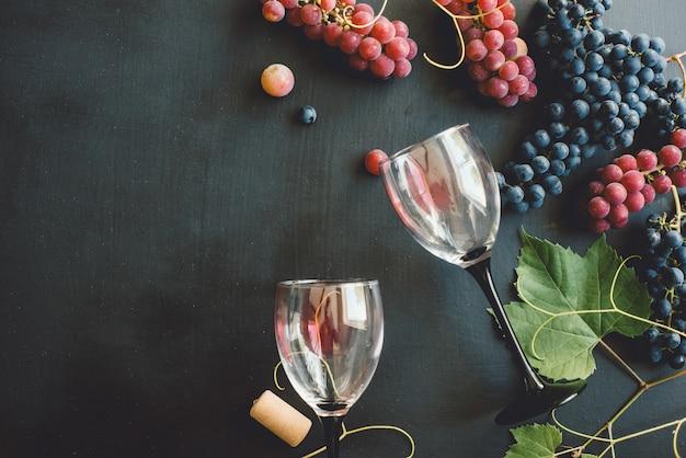 Bicchieri da vino, uva fresca, sughero e foglie
