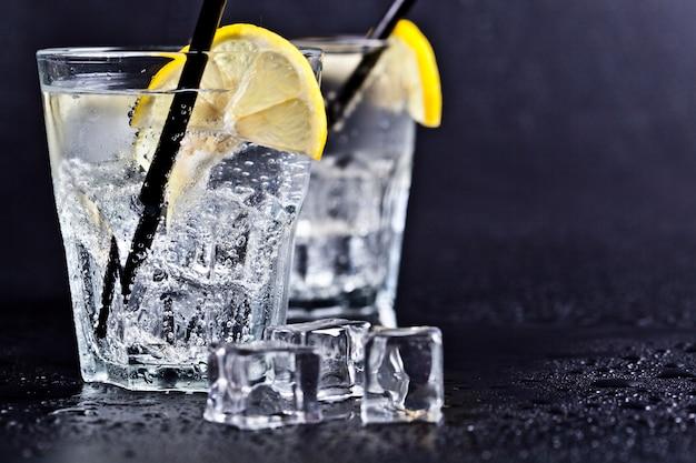 Bicchieri di acqua gassata fredda fresca con cubetti di ghiaccio e fette di limone
