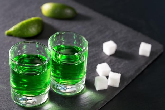 Bicchieri di assenzio con lime e zucchero