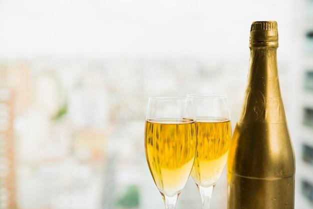 Bicchieri di bibita vicino bottiglia di alcol
