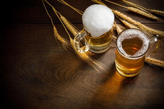 Bicchieri di birra chiara con grano sul tavolo di legno, copia spazio per il testo