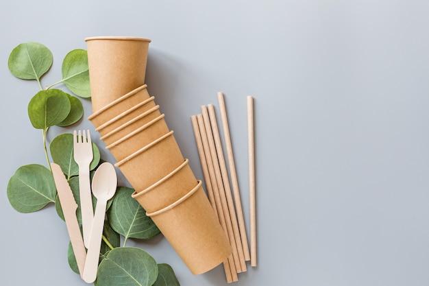 Bicchieri di carta eco naturale, cannucce, posate in legno distese su grigio