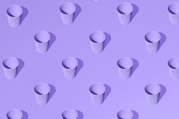 Bicchieri di carta viola in piedi su viola solido. modello