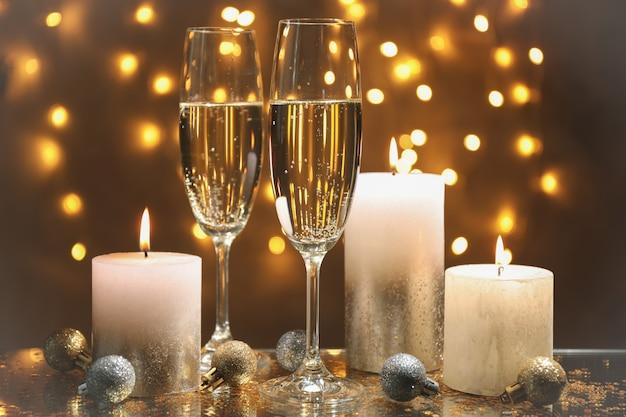 Bicchieri di champagne, candele e bagattelle contro luci sfocate spazio, spazio per il testo