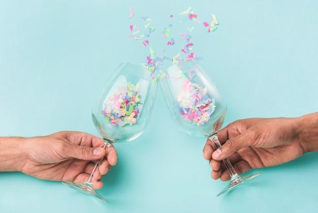 Bicchieri di champagne che si scontrano e coriandoli