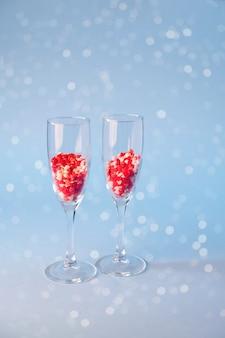 Bicchieri di champagne con caramelle di zucchero a forma di cuore rosso. su sfondo blu. concetto di celebrazione di san valentino, anniversario o matrimonio. copia spazio.