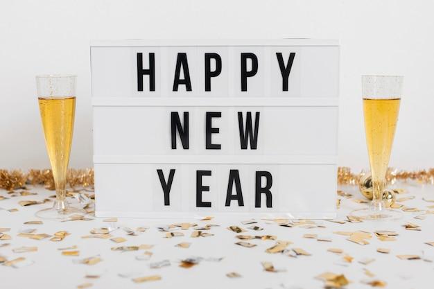 Bicchieri di champagne con segno di felice anno nuovo