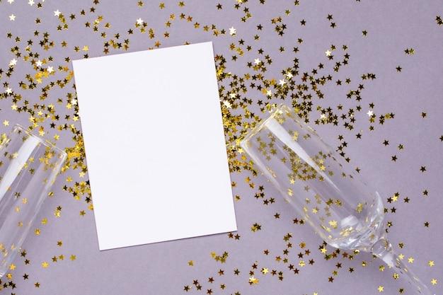 Bicchieri di champagne con stelle dorate coriandoli e carta bianca su grigio