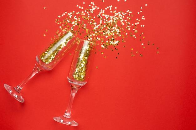 Bicchieri di champagne con stelle dorate coriandoli, natale e capodanno concetto