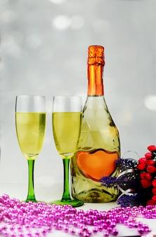 Bicchieri di champagne e una bottiglia attorno alle decorazioni