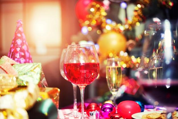 Bicchieri di champagne rosso sul tavolo con scatole regalo. buon natale, felice anno nuovo celebratio