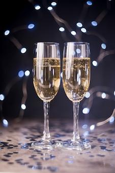 Bicchieri di champagne sul tavolo con coriandoli d'argento in discoteca
