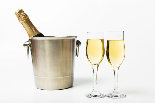 Bicchieri di champagne una bottiglia nel secchio