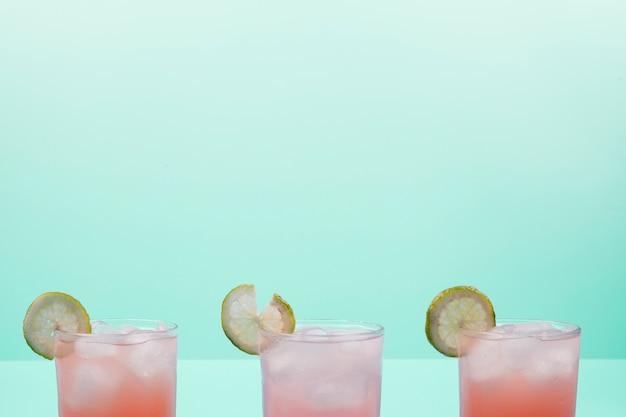 Bicchieri di cocktail con fette di limone e cubetti di ghiaccio su sfondo di menta