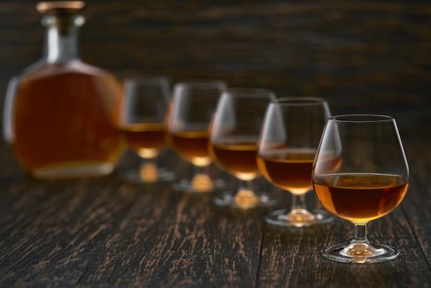 Bicchieri di cognac su un tavolo di legno con la silhouette di una bottiglia di cognac.