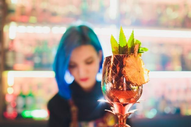 Bicchieri di metallo di freschi cocktail estivi decorati con frutta e fumi sul bancone del bar.