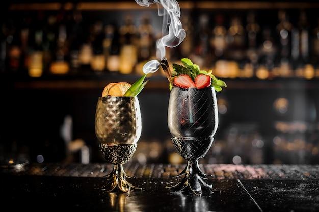 Bicchieri di metallo di freschi cocktail estivi decorati con frutta sul bancone del bar