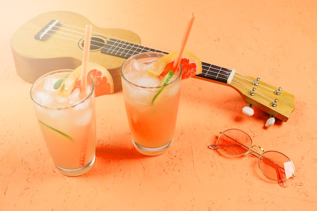 Bicchieri di succo di agrumi con cubetti di ghiaccio; occhiali da sole e ukulele su uno sfondo con texture arancione