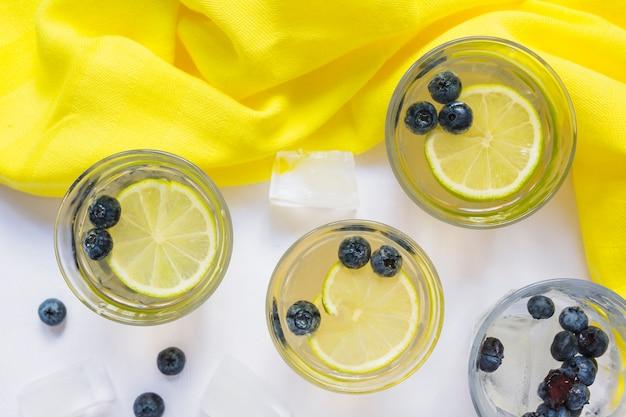 Bicchieri di succo di limone con mirtilli e cubetti di ghiaccio su sfondo bianco
