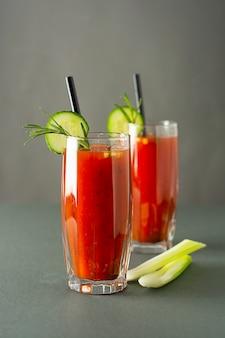 Bicchieri di succo di pomodoro gustoso isolato sul tavolo grigio