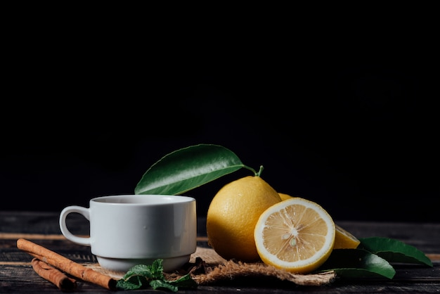 Bicchieri di tè con limone, fette di limoni su un tagliere