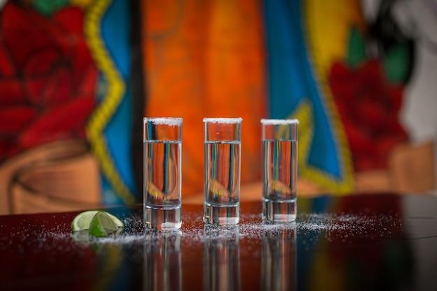 Bicchieri di tequila, sale e limone su sfondo colorfull messicano