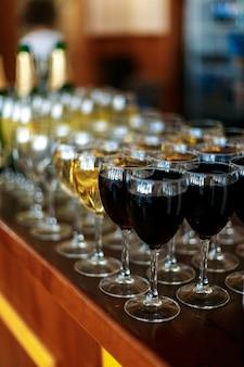 Bicchieri di vino bianco e bottiglia di vino rosso