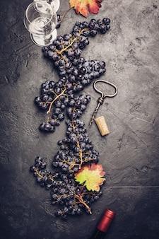 Bicchieri di vino con uva e tappi su sfondo scuro