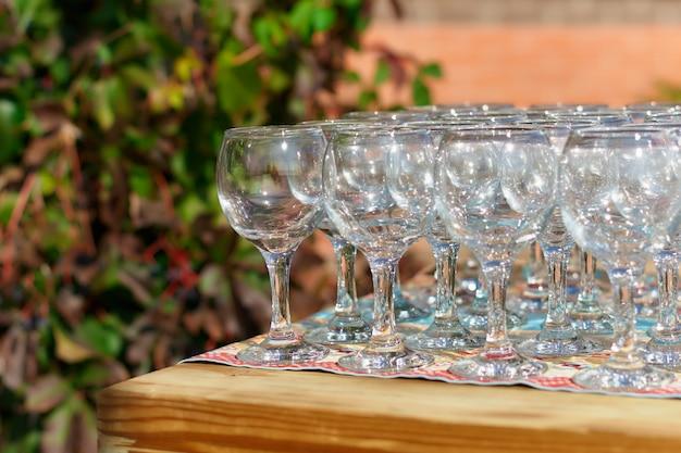 Bicchieri di vino da tavola bella vacanza due file di bicchieri su un tavolo con una tovaglia bianca su bicchieri alti posizionati un bicchiere di vino sul tavolo festivo