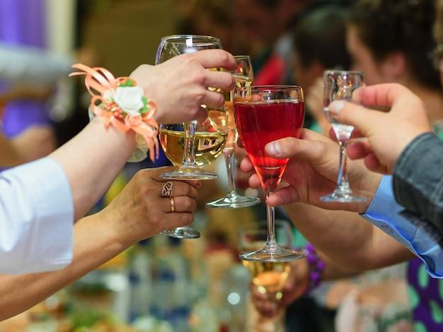 Bicchieri di vino nelle mani degli amici che celebrano la festa