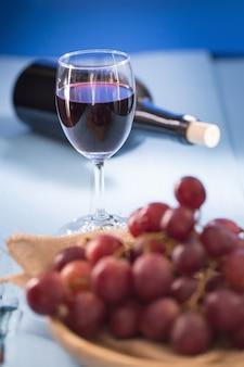 Bicchieri di vino rosso con uva rossa e una bottiglia di vino su sfondo blu.