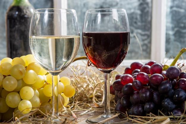 Bicchieri di vino rosso e bianco con uva