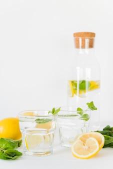 Bicchieri e bottiglia con bevanda al limone e menta