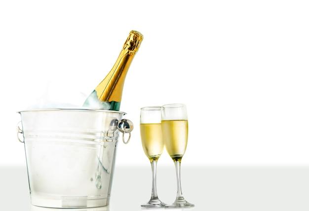 Bicchieri e bottiglia di champagne nel secchiello del ghiaccio