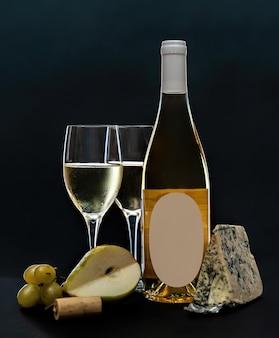 Bicchieri e bottiglia di vino bianco con formaggio a muffa blu e frutta