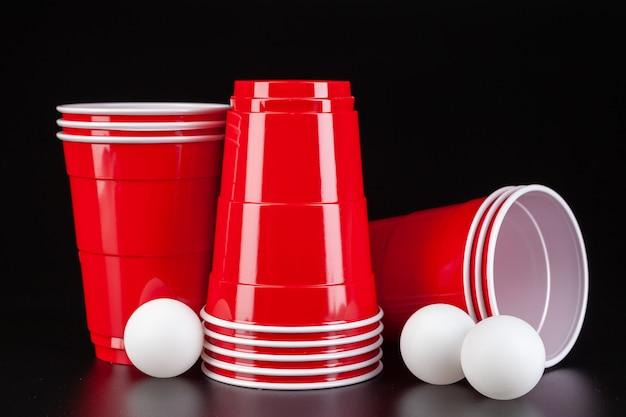 Bicchieri e palla di plastica rossi per il gioco del beer pong