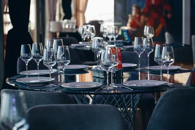 Bicchieri, forchetta fiore, coltello servito per cena in ristorante con interni accoglienti