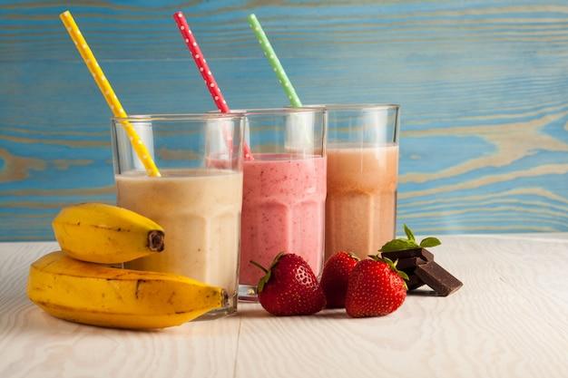 Bicchieri lunghi di frappè con cioccolato, fragola, banana, con gelato su bianco