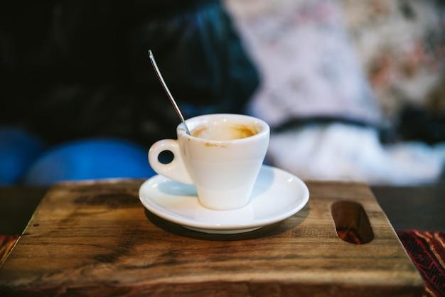 Bicchierino vuoto di arabica espresso con macchia di caffè servito su tavola di legno.