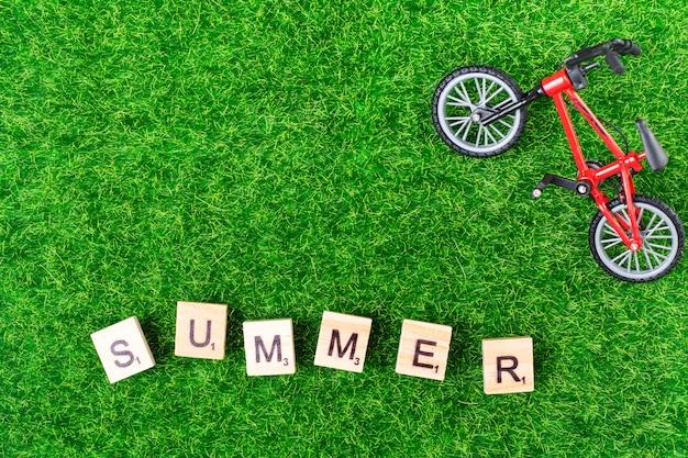 Bici giocattolo e lettere su erba