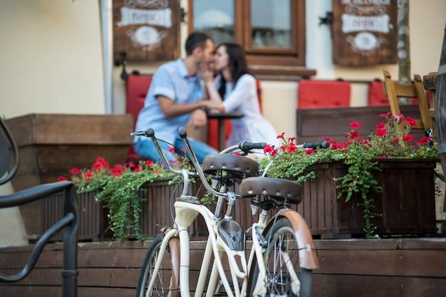 Bici in tandem d'annata vicino ai letti di legno con i fiori rossi su un fondo vago che bacia le giovani coppie