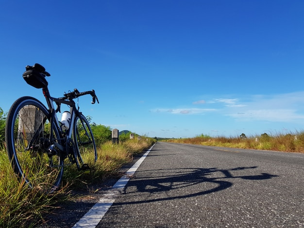 Bici parcheggiata accanto alla strada aperta con cielo blu. concetto di libertà e trasporto.