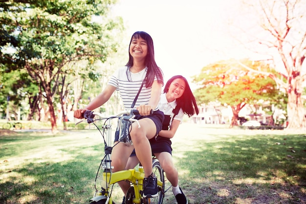 Bicicletta asiatica allegra di guida dell'adolescente in parco pulbic