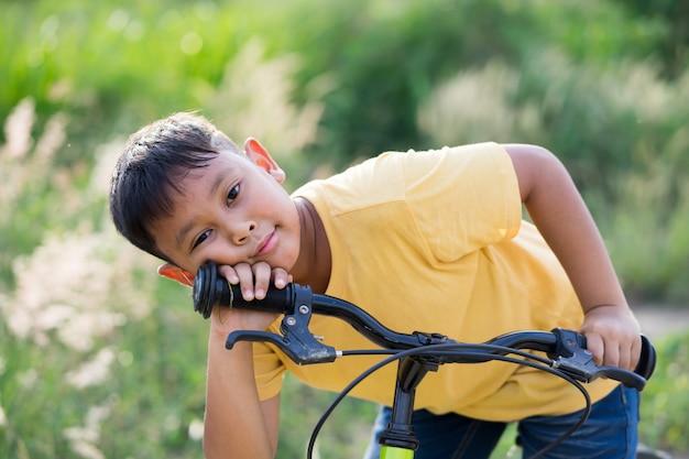 Bicicletta asiatica di giro del ragazzo del bambino in natura